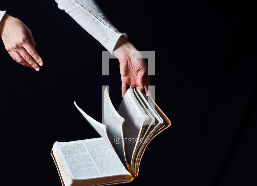 hand flipping the pages of a Bible