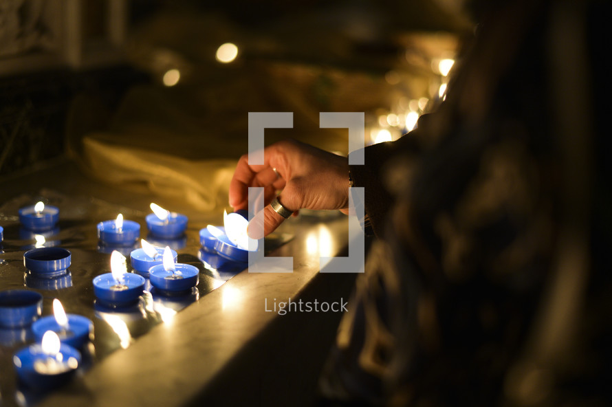 lighting votive prayer candles