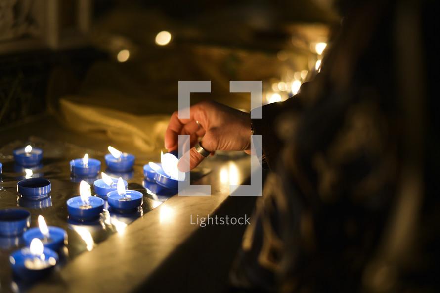 lighting votive prayer candles