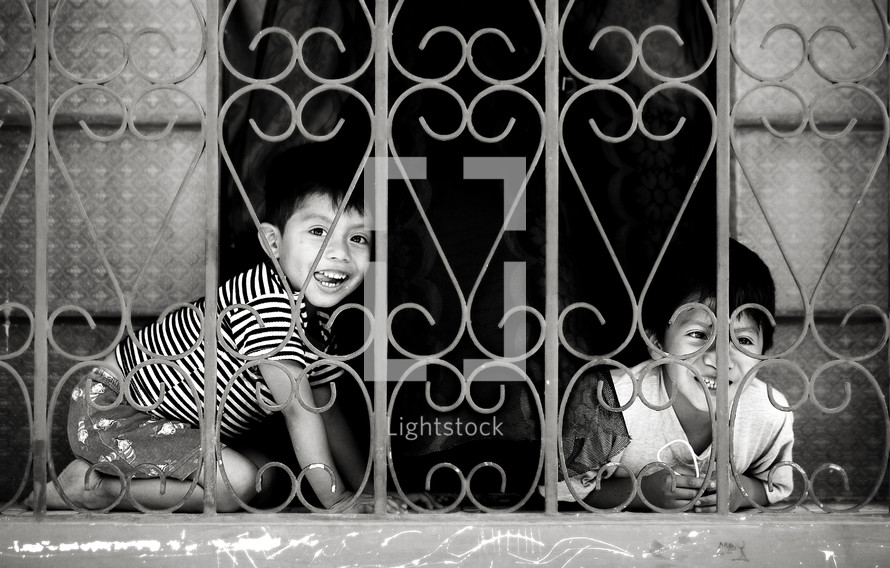 Two boys smile from a gated window