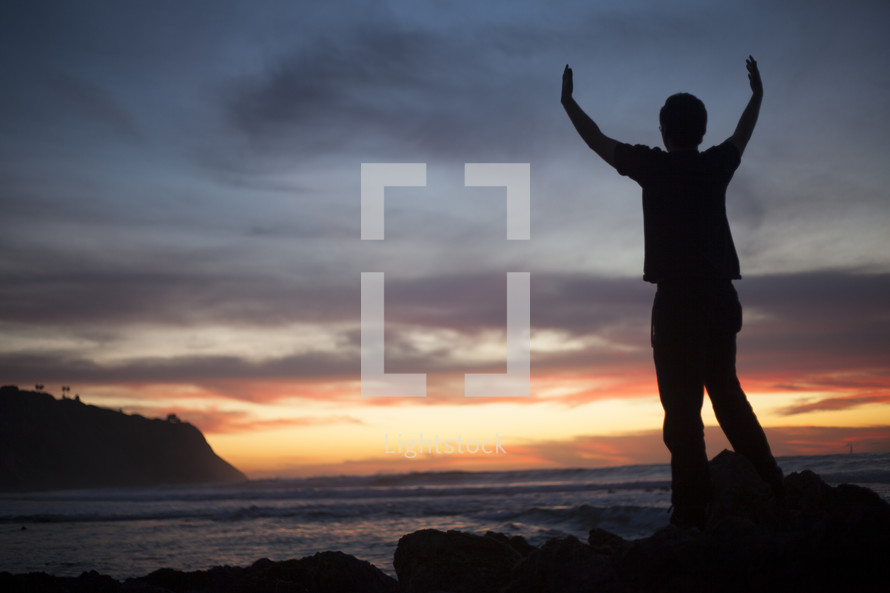 man standing in front of the ocean at sunset with hands raised in praise and worship to God