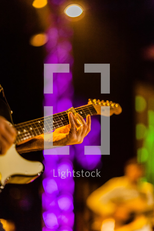 Hands playing electric guitar on lighted stage durning worship