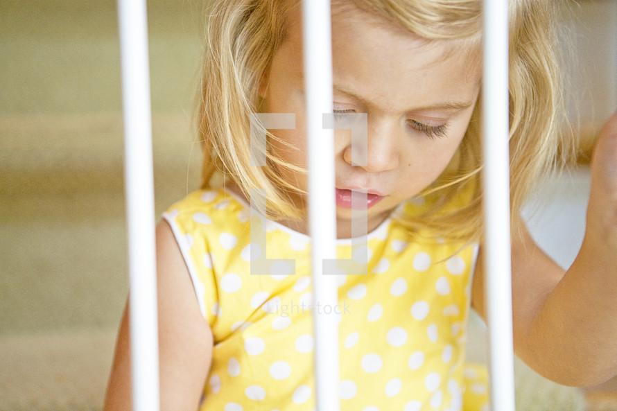 toddler girl looking through bars