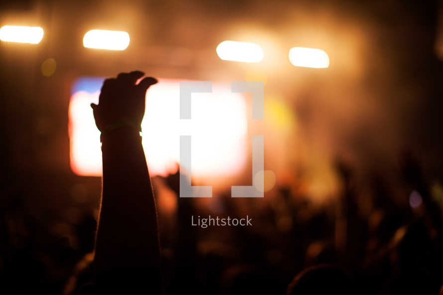 hands of an audience under concert lights