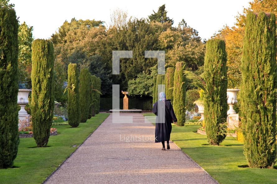 shrouded woman walking down a garden path