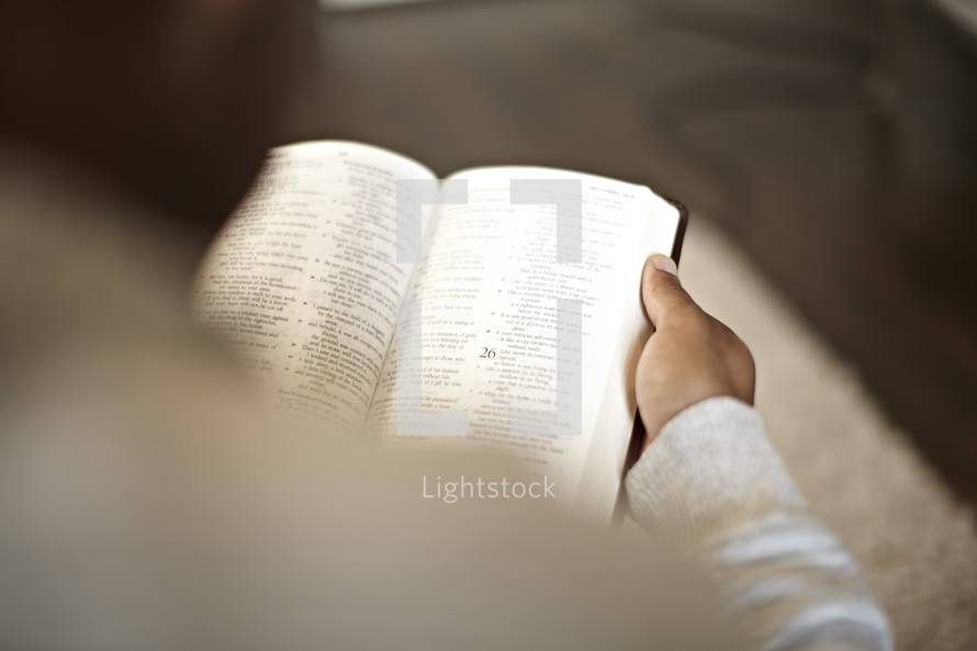 An over-the-shoulder view of a man reading the bible
