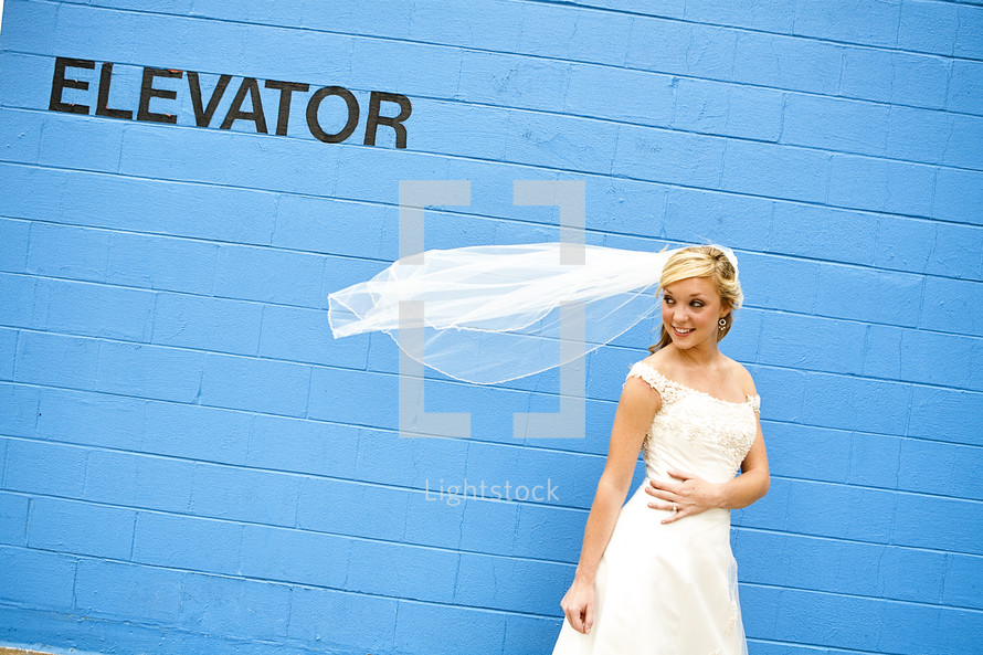 bride with her veil blowing in the wind standing in front of a blue wall