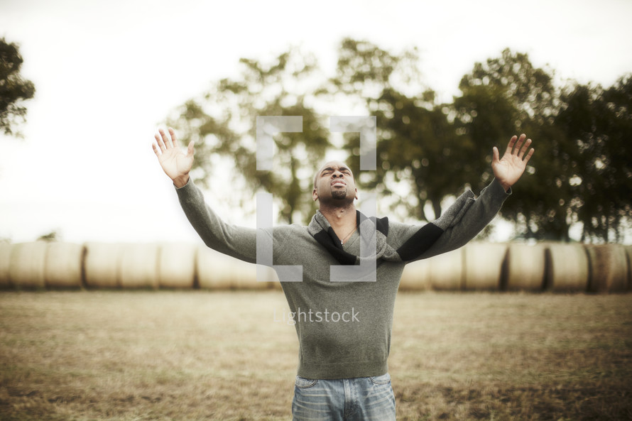 An African American man with raised hands in worship