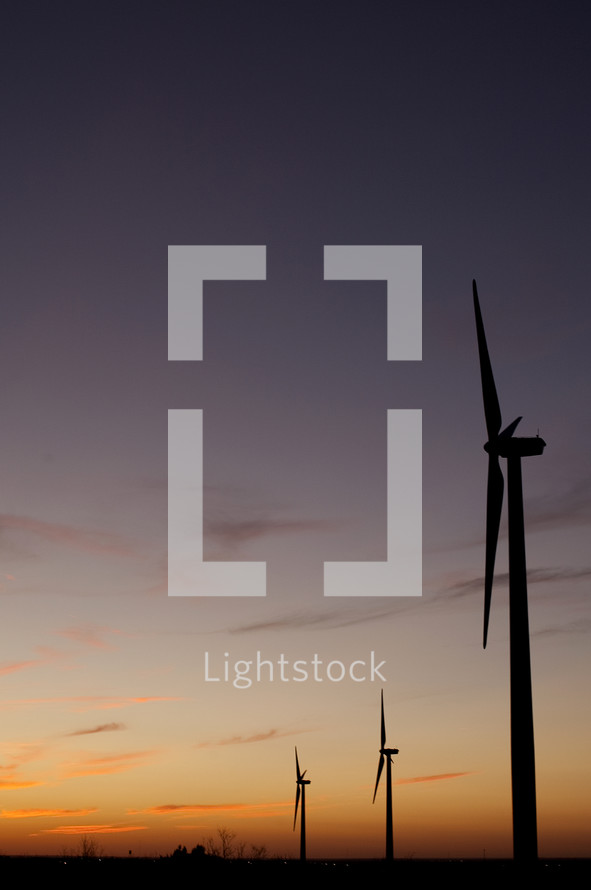 Silhouettes of windmills at sunset