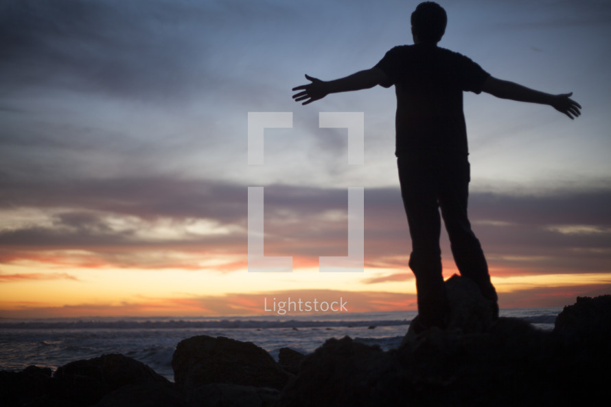 Man on beach at sunset with outstretched arms