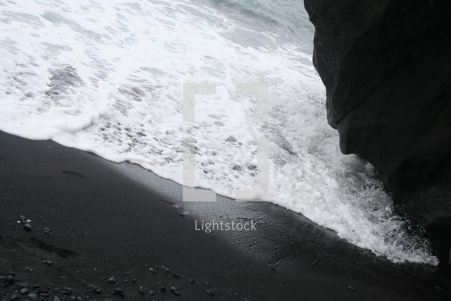 Waves against black sand