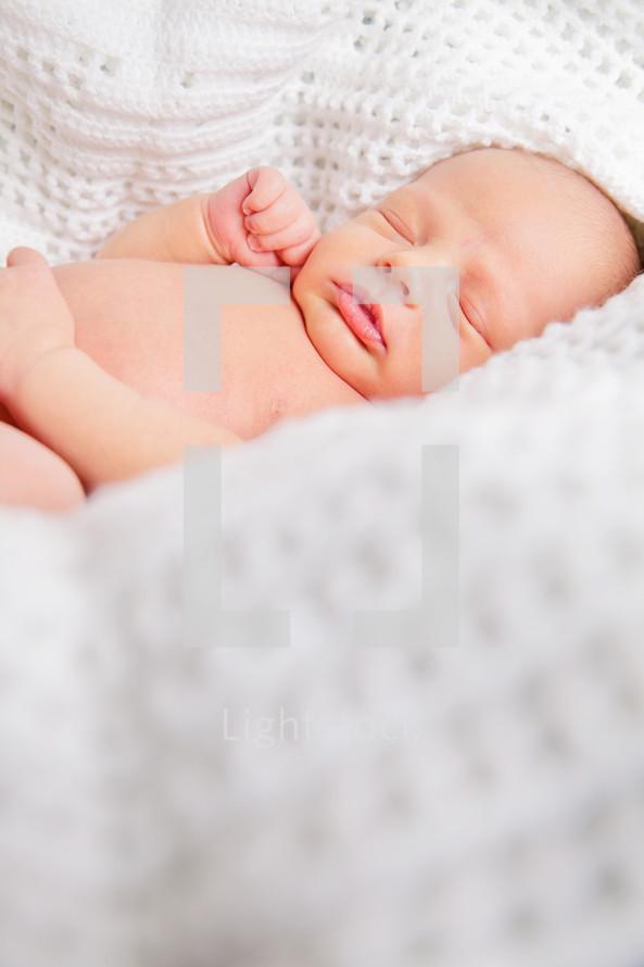 Baby lying on while crocheted blanket