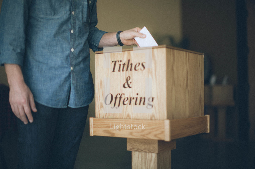 Man putting envelope into a tithes and offering box