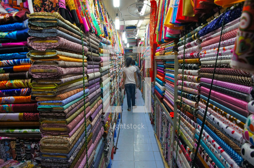 A fabric store filled with multiple colored and textured fabrics