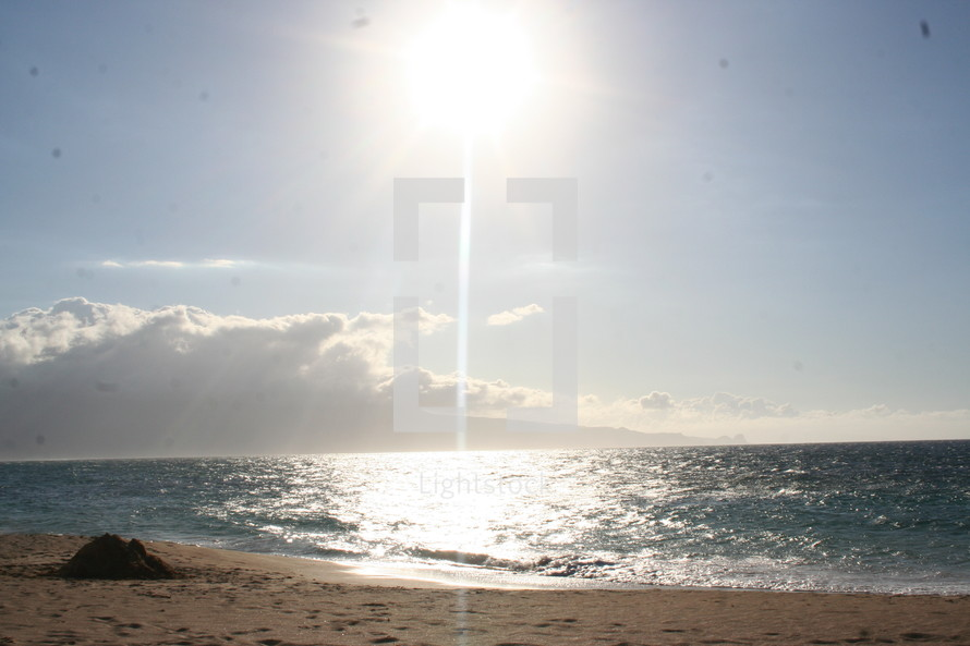 sunburst in a blue sky over a beach
