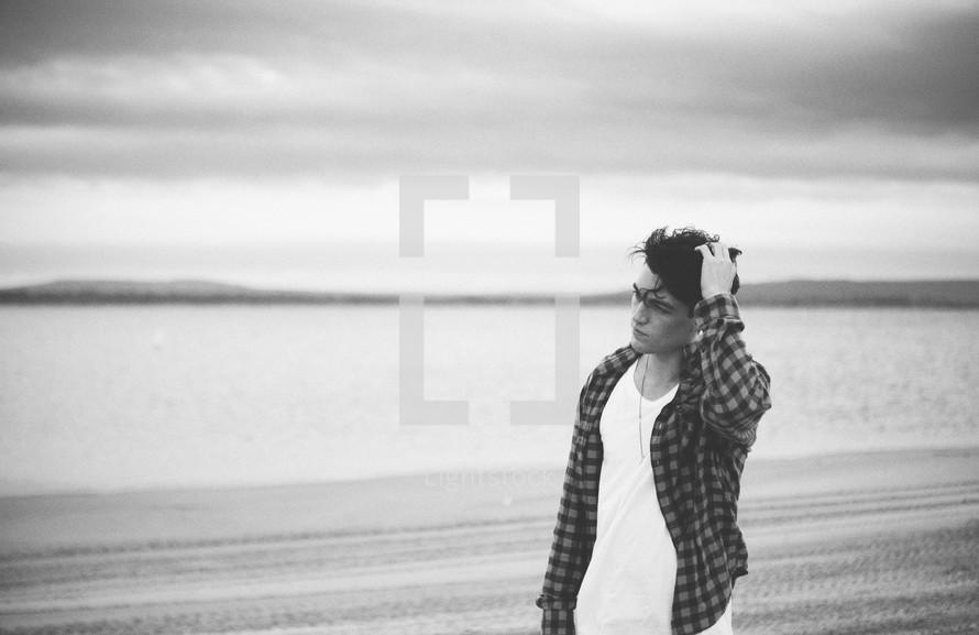 Man standing on beachfront scratching head
