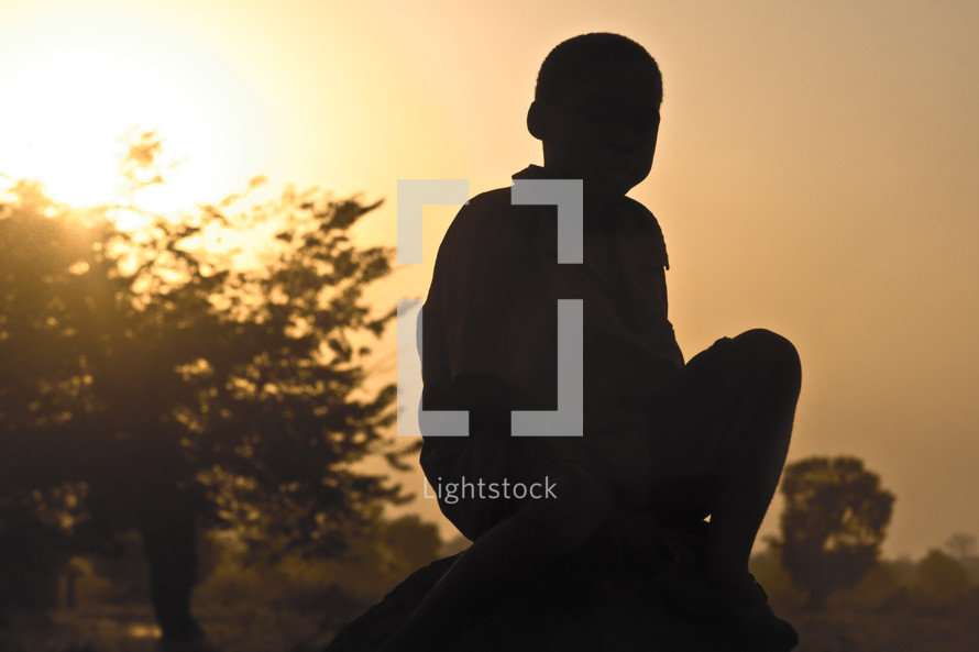 A boy sitting on a rock.