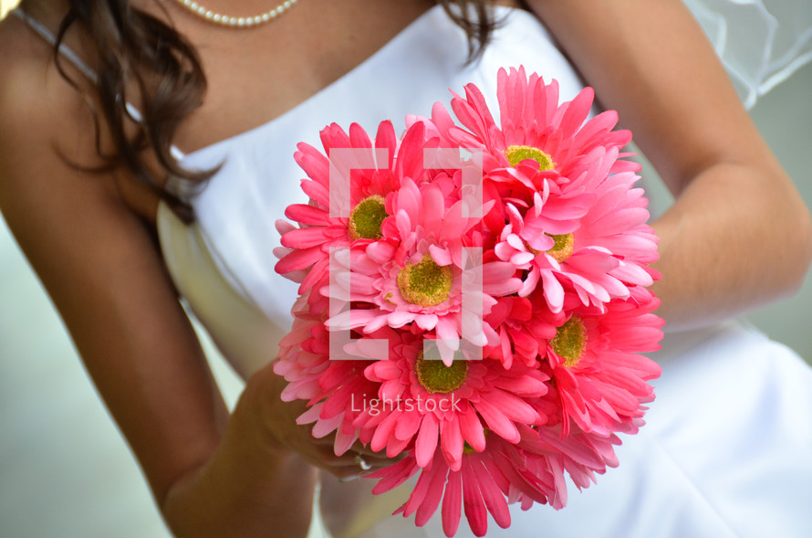 bride holding a bouquet of pink gerber daisies