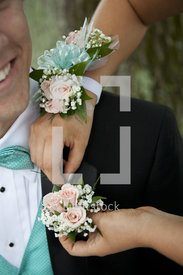 Woman hands pinning corsage on man's jacket