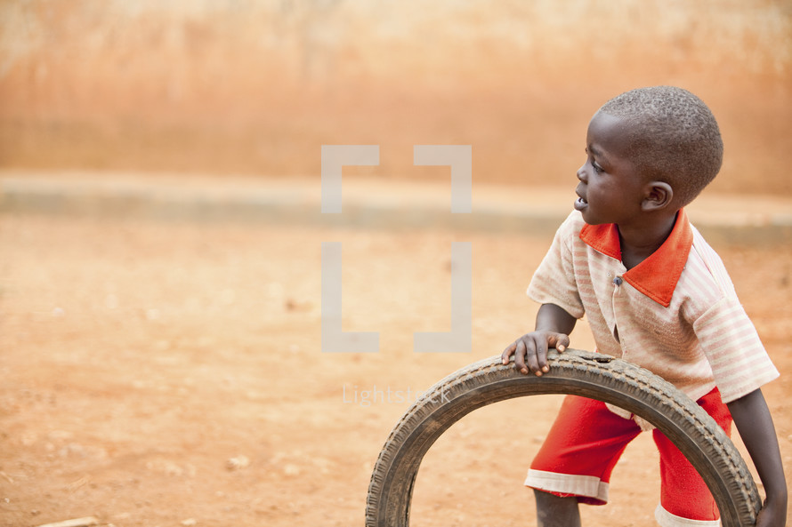 A young boy playing with a tire.