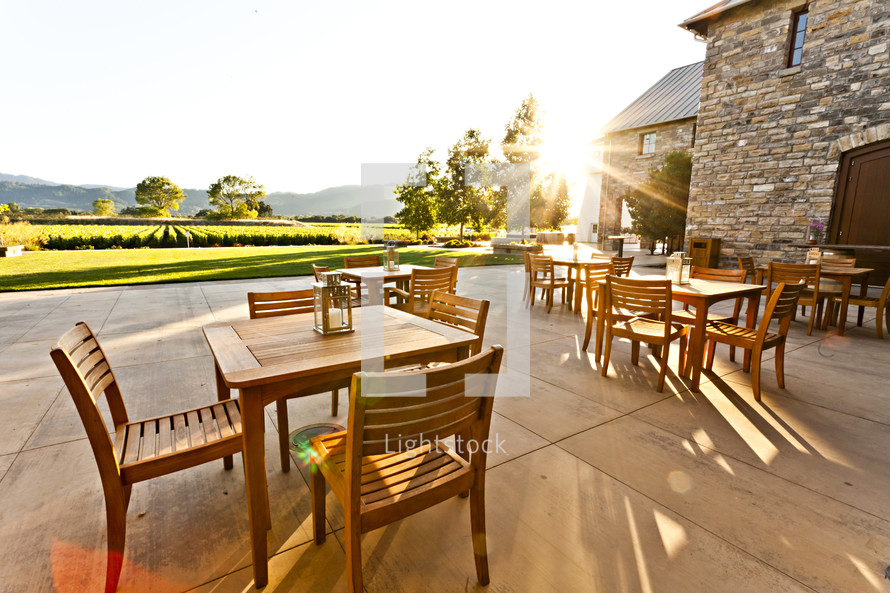 A patio with wood  tables and chairs at sunset over looking a vineyard napa valley