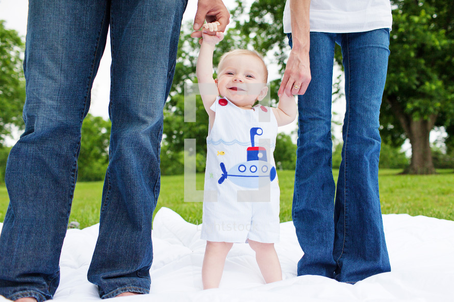 Two adults in denim jeans holding  the hands of a toddler boy standing on a white blanket in the grass in a park.