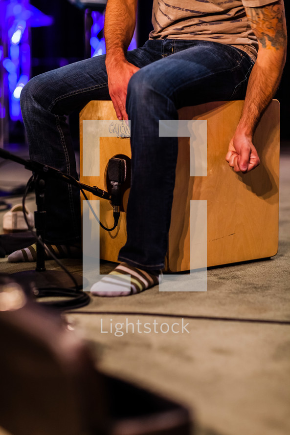 Man in jeans and socks with tattoo on arm sitting and beating on a Cajon wooden box drum on a lighted stage.