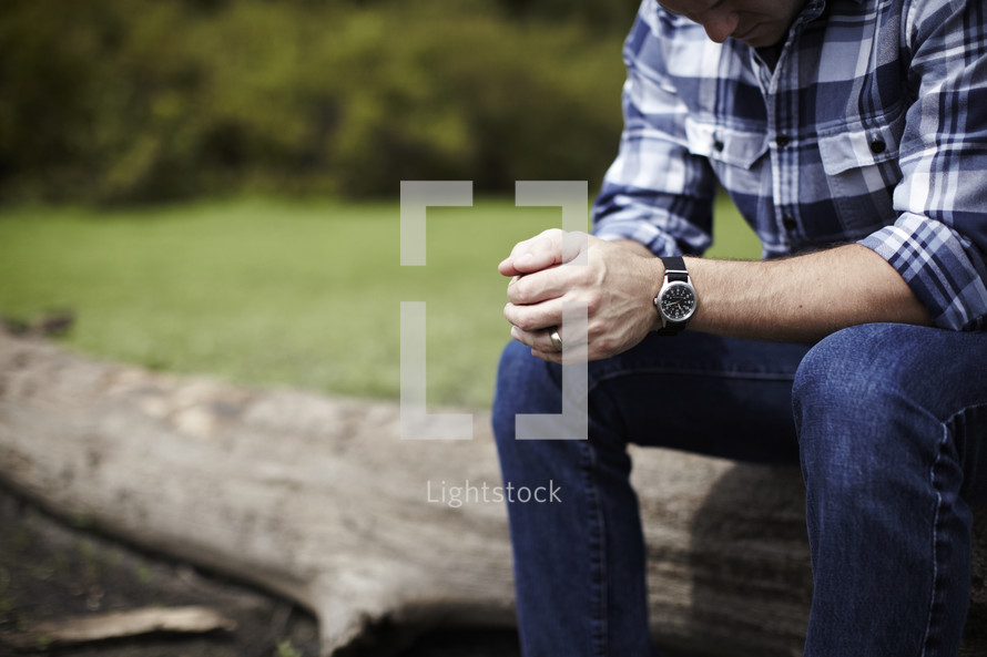 Man sitting on log praying