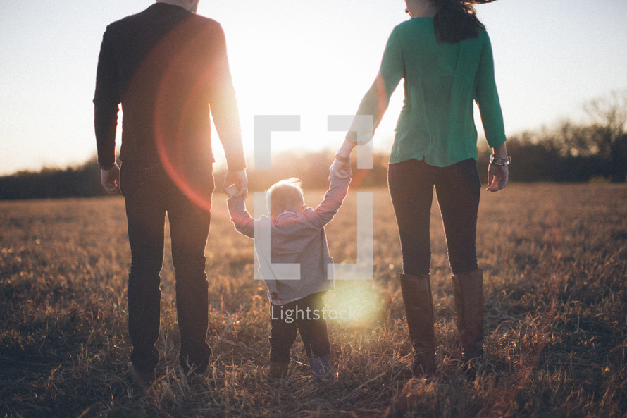 Backside view of man and woman holding the hands of a toddler child while standing in grassy field at sunrise.
