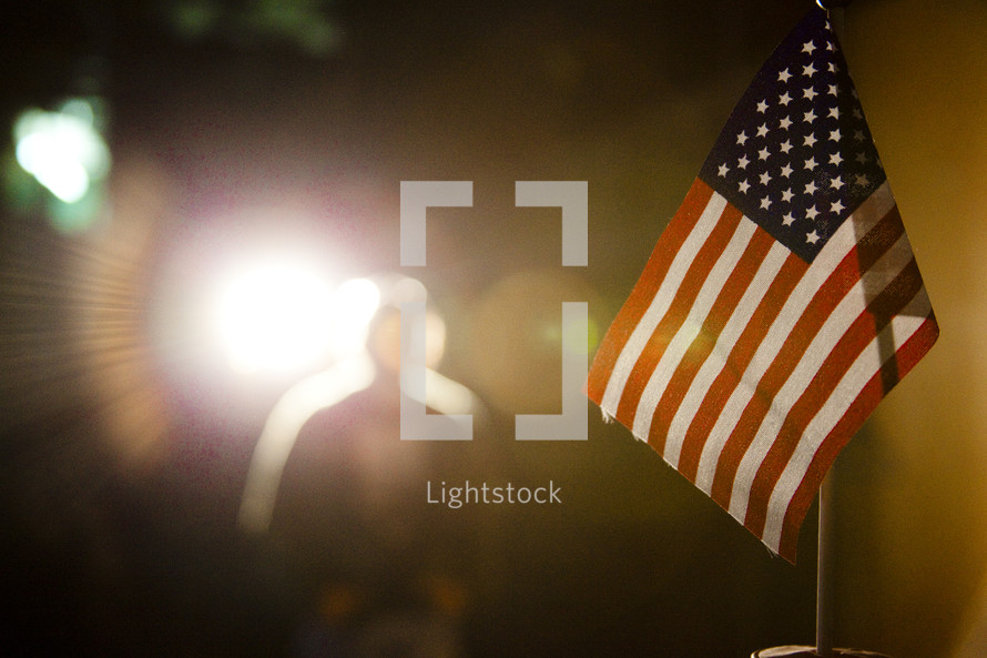 American flag with silhouette of man in lighted background.