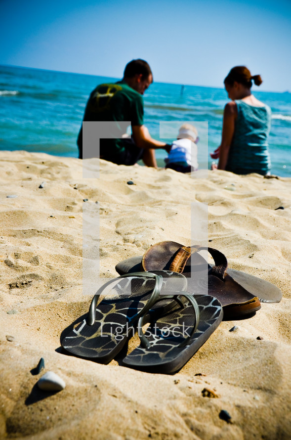 flip flops on a beach in front of a family playing in the sand