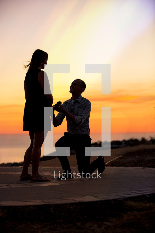 silhouette of man proposing to woman - sunset