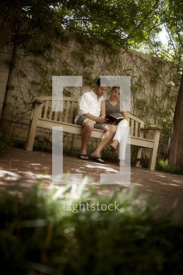A young married couple sits on a bench reading God's word.
