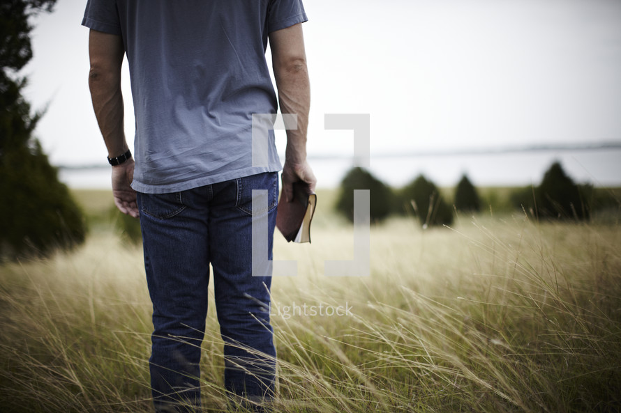 Man standing in field holding  a bible