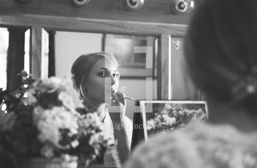 Woman looking in mirror applying lipstick