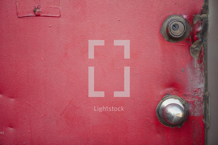 dents in a red metal door
