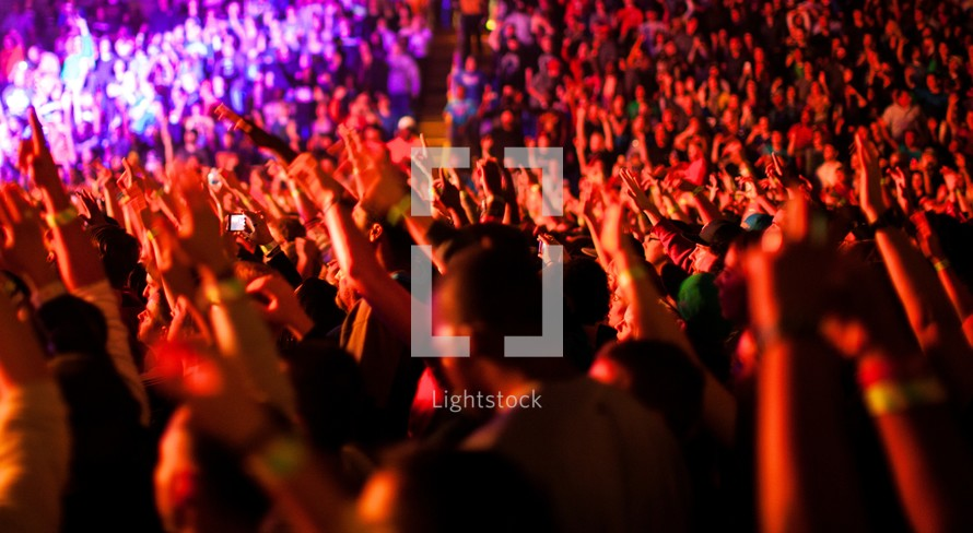 audience hands raised at a concert