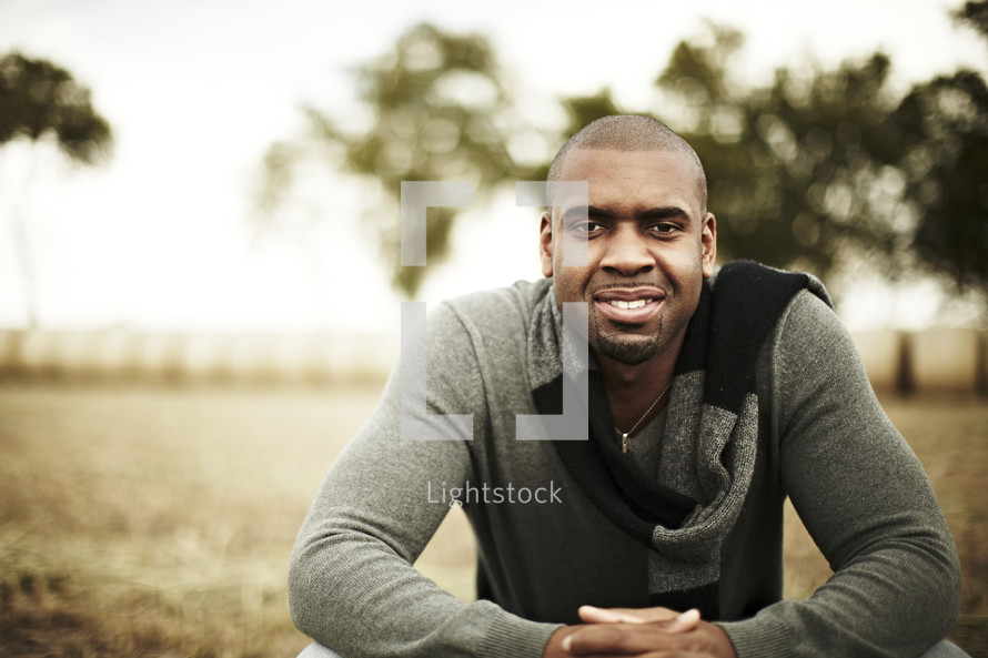 Man sitting in a field smiling
