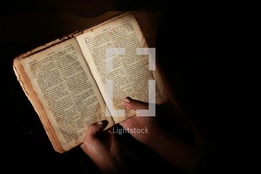 Woman reading old worn Bible