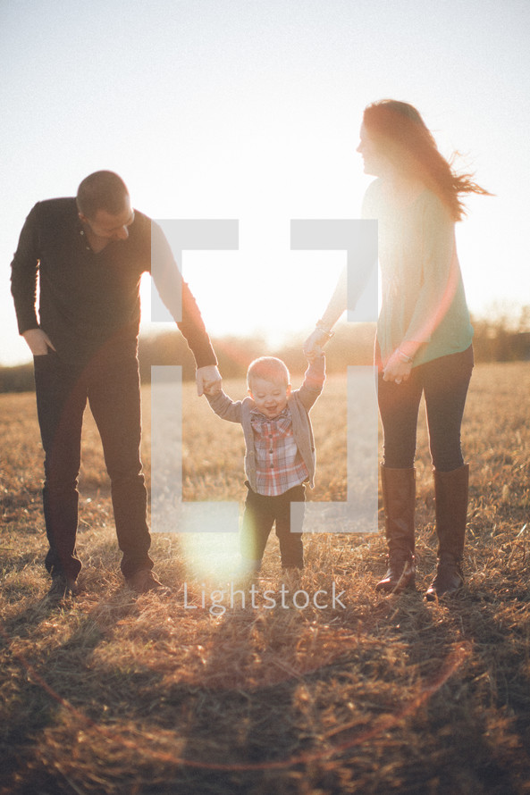 Man and woman holding hands of toddler child in grassy field at sunset.