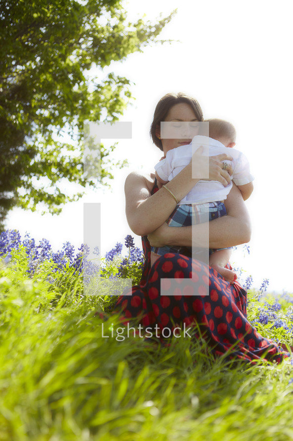 A woman holding her baby in a field of flowers
