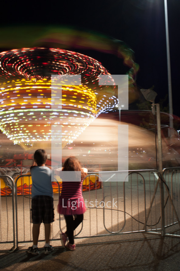 Children watching a ride from outside the fence