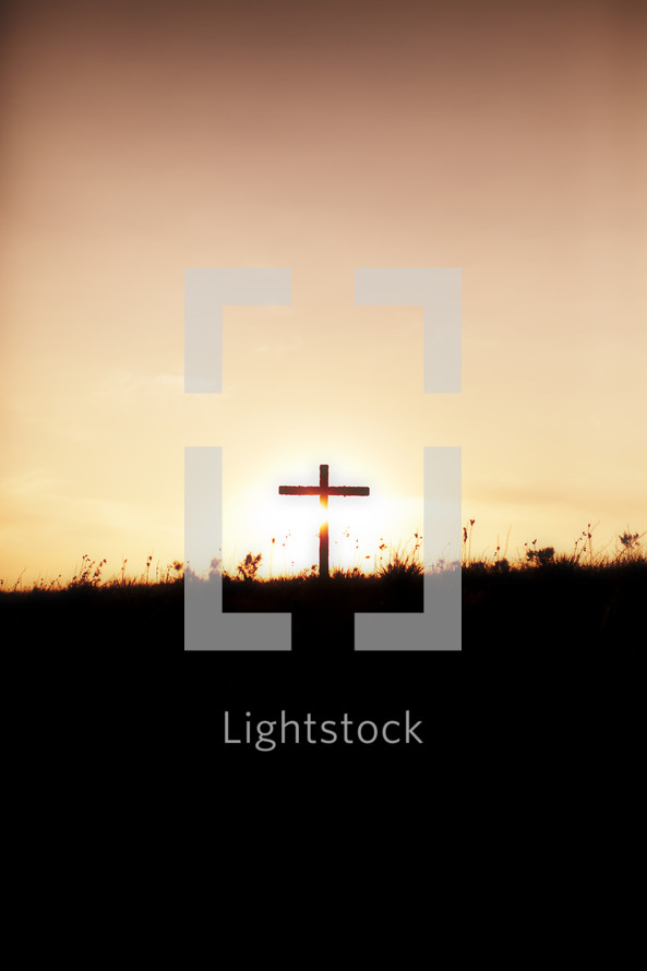 A silhouetted cross on the horizon at sunrise