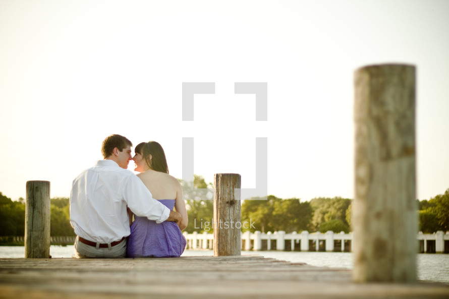 couple sitting and kissing at the end of a dock
