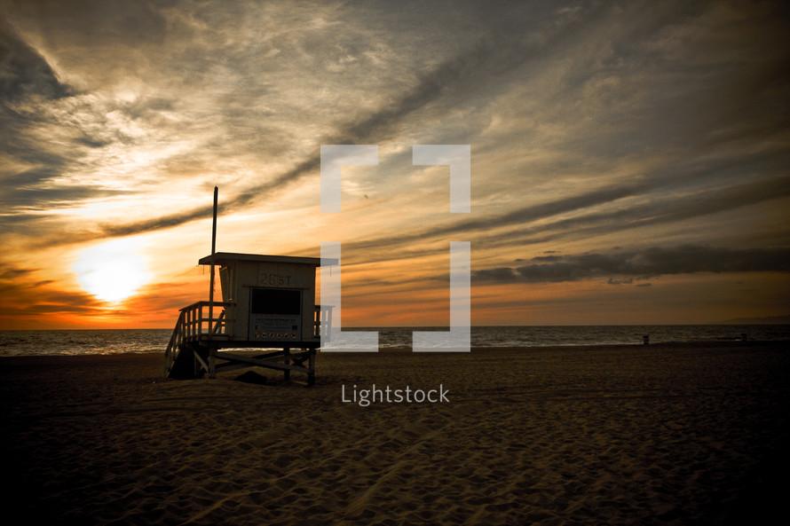 lifeguard stand on a beach at sunset