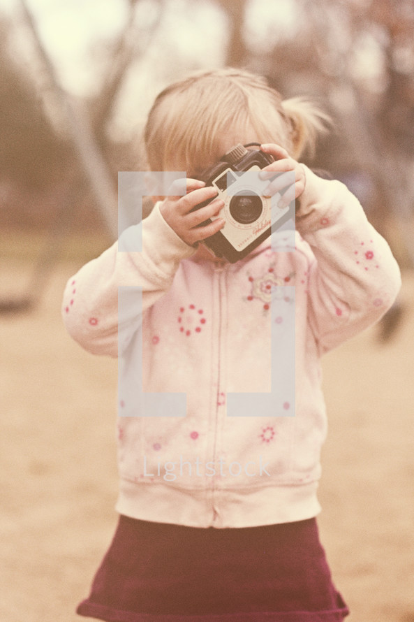 A little girl looking through a camera.