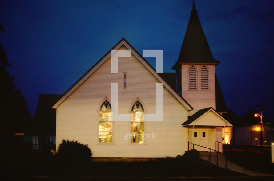 A white church against a night  sky.
