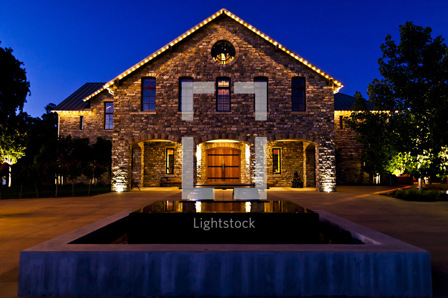 lighted stone building with wooden doors  sunset blue hour reflection fountain water night winery