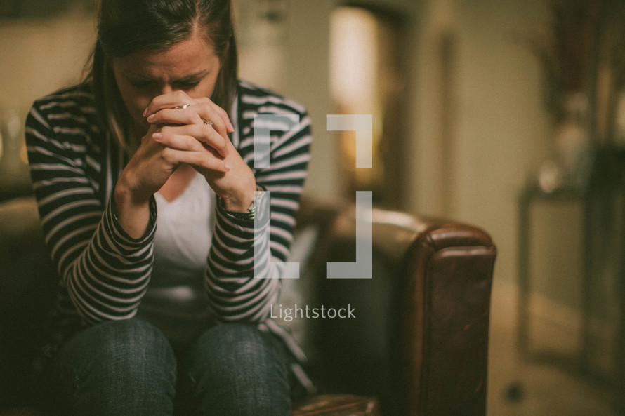 woman with her head bowed and fingers laced in prayer