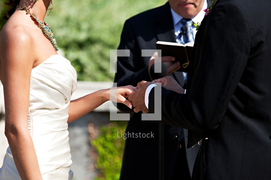 Groom placing ring on bride's hand during outdoor wedding ceremony.